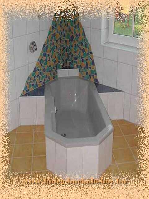 Hagyományokkal szakított elrendezésü fürdőszoba kád hátterében mozaik burkoló lapokkal.