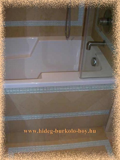 Fürdőszobban a beépített kád hangsúlyosabb látványt nyújt, amennyiben a környezetétől eltérő méretü lapokkal van burkolva, mint ezen a képen mozaik burkoló lapokkal.