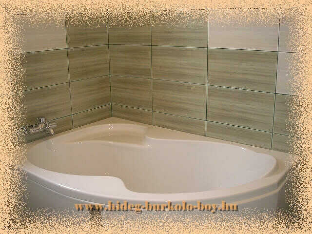 A kád gyári előlappal szerelt és a hátteret adó burkolás szin mintázata egyedi hangsúly teremt a fürdőszoba saroknak.