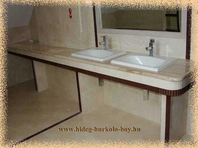 Ebben a fürdőszobában érdemes volt a teljes falszakaszt beépíteni és mosdó pultot készíteni