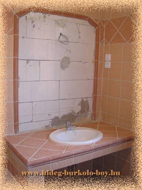 Fürdőszobai kád mellé épített mosdó kerettel határolt beépített tükröt is kapott, tágítva a teret.